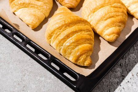 baked delicious croissants on baking tray on concrete grey surface