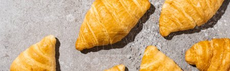 top view of fresh baked croissants on concrete grey surface, panoramic shot