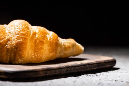 close up view of fresh baked croissant on wooden cutting board on concrete grey surface isolated on black
