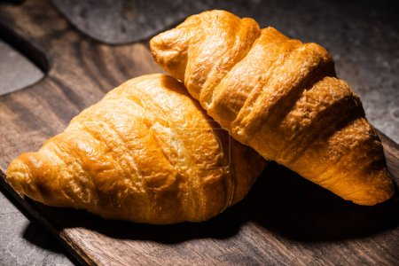 Photo for Fresh baked croissants on wooden cutting board on concrete grey surface in dark - Royalty Free Image