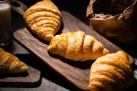 Photo for Selective focus of fresh baked croissants on towel and wooden cutting board near paper bag and milk on concrete grey surface in dark - Royalty Free Image