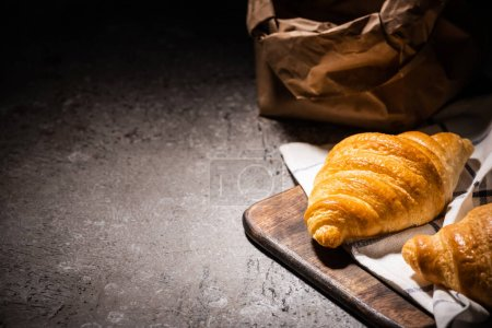 Photo for Selective focus of fresh baked croissants on towel and wooden cutting board near paper bag on concrete grey surface in dark - Royalty Free Image
