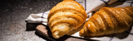 Photo for Fresh baked croissants on towel and wooden cutting board on concrete grey surface in dark, panoramic shot - Royalty Free Image