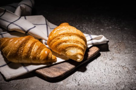 Photo for Fresh baked croissants on towel and wooden cutting board on concrete grey surface in dark - Royalty Free Image
