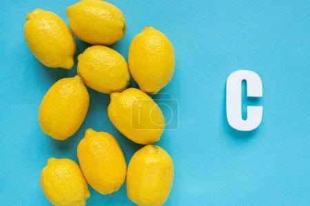 Photo pour Vue du dessus des citrons jaunes mûrs et lettre C sur fond bleu - image libre de droit