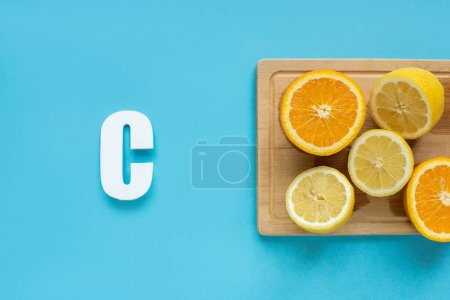 Photo for Top view of ripe cut lemon and orange on wooden cutting board near letter C on blue background - Royalty Free Image