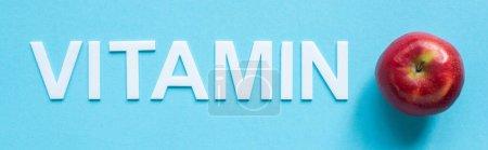 Photo pour Vue du dessus de pomme rouge mûre et mot vitamine sur fond bleu, panoramique - image libre de droit
