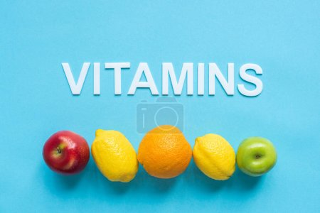 top view of ripe fruits in line and word vitamins on blue background