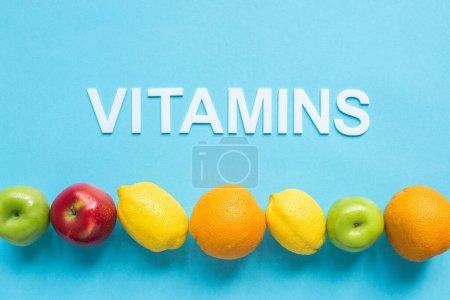 vue du haut des fruits mûrs en ligne et mot vitamines sur fond bleu
