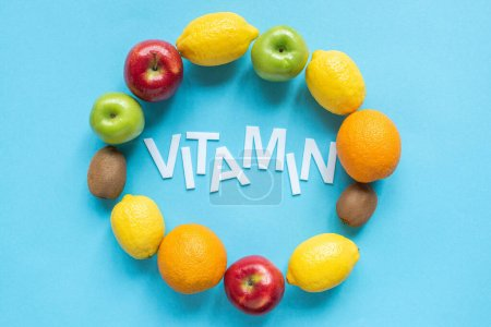 Photo for Top view of ripe fruits around word vitamin on blue background - Royalty Free Image