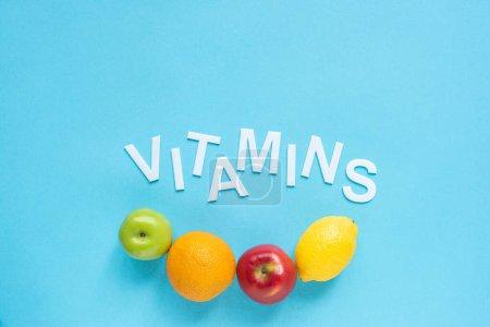Photo pour Vue du dessus des fruits mûrs et des vitamines de mot sur fond bleu - image libre de droit