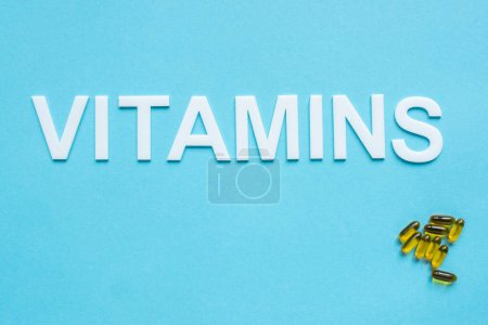 top view of pills and word vitamins on blue background