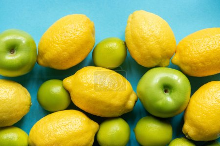 top view of ripe yellow lemons and green apples and limes on blue background
