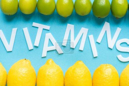 Photo pour Vue du dessus des citrons jaunes mûrs et des citrons verts sur fond bleu avec des vitamines mot - image libre de droit