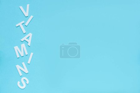 top view of word vitamins on blue background