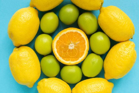top view of ripe yellow lemons, orange and limes arranged in circles on blue background