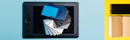 Photo pour Collage d'échantillons de couleurs sur tablette graphique et carnet avec crayons sur fond bleu et jaune - image libre de droit