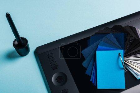 Photo pour Vue grand angle des échantillons de couleur, tablette graphique et stylet sur fond bleu - image libre de droit