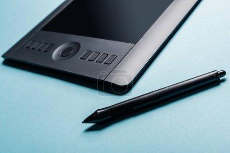 Photo pour Vue rapprochée du stylet et de la tablette graphique sur fond bleu - image libre de droit