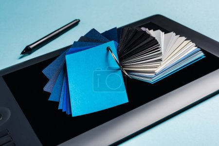 Nahaufnahme von Farbmustern auf Grafik-Tablet und Stift auf blauem Hintergrund