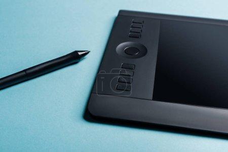 Photo pour Vue rapprochée de la tablette graphique et du stylet sur la surface bleue - image libre de droit