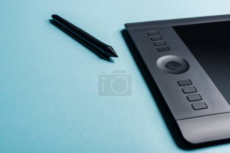 Photo for Close up view of stylus near graphics tablet on blue background with copy space - Royalty Free Image