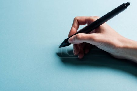 Photo for Cropped view of designer holding stylus of graphics tablet on blue background - Royalty Free Image
