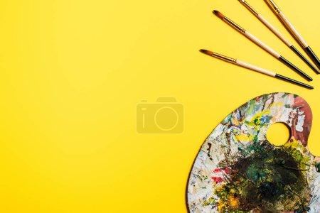 Photo pour Vue du dessus des pinceaux et palette avec coups de pinceau sur la surface jaune - image libre de droit