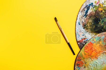 Photo pour Vue du dessus du pinceau à dessin et des palettes sur surface jaune - image libre de droit