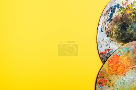 Photo for Top view of palettes in paints on yellow surface - Royalty Free Image