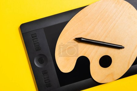 Photo for Top view of wooden palette and graphics tablet with stylus on yellow surface - Royalty Free Image