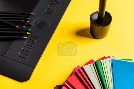 Foto de Cerrar la vista de los cambios de color, la tabla gráfica y los lápices de color en la superficie amarilla. - Imagen libre de derechos