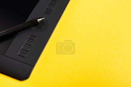 Photo pour Vue rapprochée du stylet sur tablette graphique sur fond jaune - image libre de droit