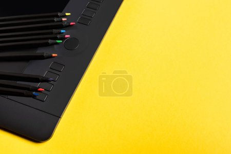 Photo pour Vue rapprochée des crayons de couleur sur la tablette graphique sur la surface jaune - image libre de droit