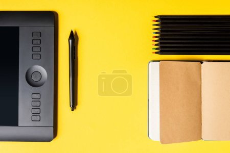 Photo pour Vue du dessus de la tablette graphique et du stylet près du bloc-notes ouvert et des crayons de couleur sur la surface jaune - image libre de droit
