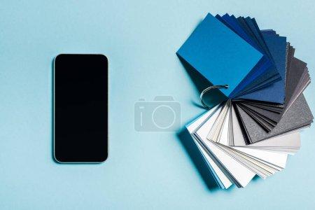 Ansicht des Smartphones von oben mit leerem Bildschirm und Farbmustern auf blauem Hintergrund