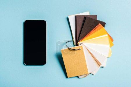 Photo pour Vue du dessus des échantillons colorés et smartphone avec écran blanc sur fond bleu - image libre de droit