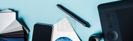 Photo for Panoramic shot of graphics tablet, smartphone and color samples on blue background - Royalty Free Image