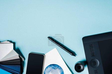 Photo pour Vue du dessus du smartphone, échantillons de couleur avec tablette graphique et dessin à l'aquarelle sur fond bleu - image libre de droit