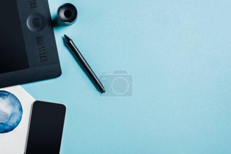 Photo pour Vue du dessus de la tablette graphique, dessin à l'aquarelle et smartphone sur la surface bleue - image libre de droit