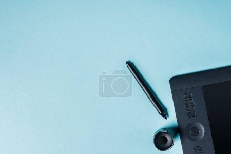 Photo pour Vue du dessus de la tablette graphique avec stylet sur fond bleu - image libre de droit
