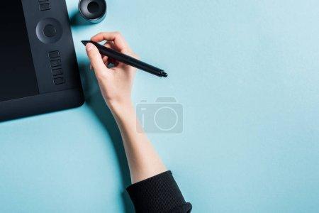 Photo pour Vue du dessus du stylet du concepteur tenant près de la tablette graphique sur fond bleu - image libre de droit