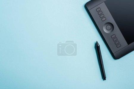 Photo pour Vue du dessus du stylet près du tampon de dessin sur fond bleu avec espace de copie - image libre de droit