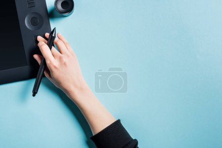 Photo for Top view of designer holding stylus and using graphics tablet on blue background - Royalty Free Image