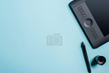 Top view of graphics tablet near stylus and stand on blue background