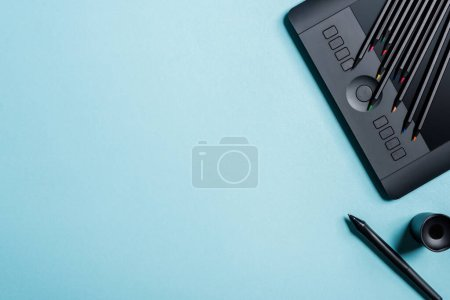 Photo for Top view of color pencils on graphics tablet and stylus on blue background - Royalty Free Image