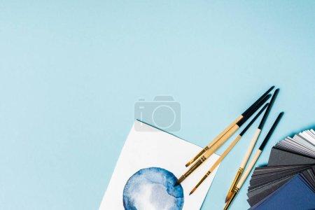 Foto de Vista superior de pinceles en acuarela y muestras de color sobre fondo azul - Imagen libre de derechos