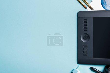 Photo pour Vue du dessus de la tablette graphique près des pinceaux et peinture à l'aquarelle sur fond bleu - image libre de droit