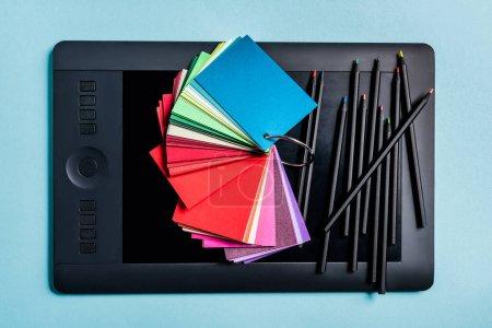 Ansicht von Farbmustern und Bleistiften auf dem Grafik-Tablet auf blauem Hintergrund