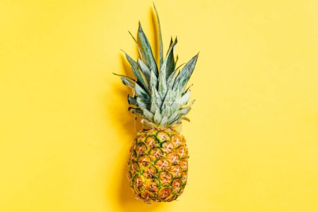 top view of fresh ripe pineapple on yellow background